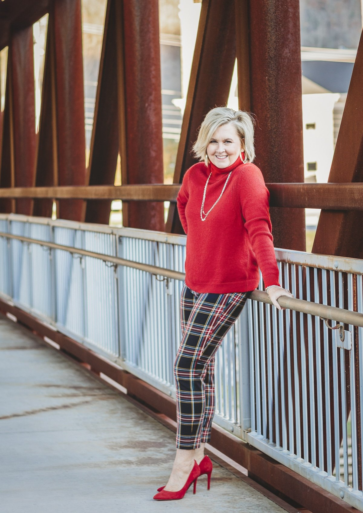 Fashion Blogger 50 Is Not Old is looking festive in this red turtleneck sweater and plaid pants with red heels