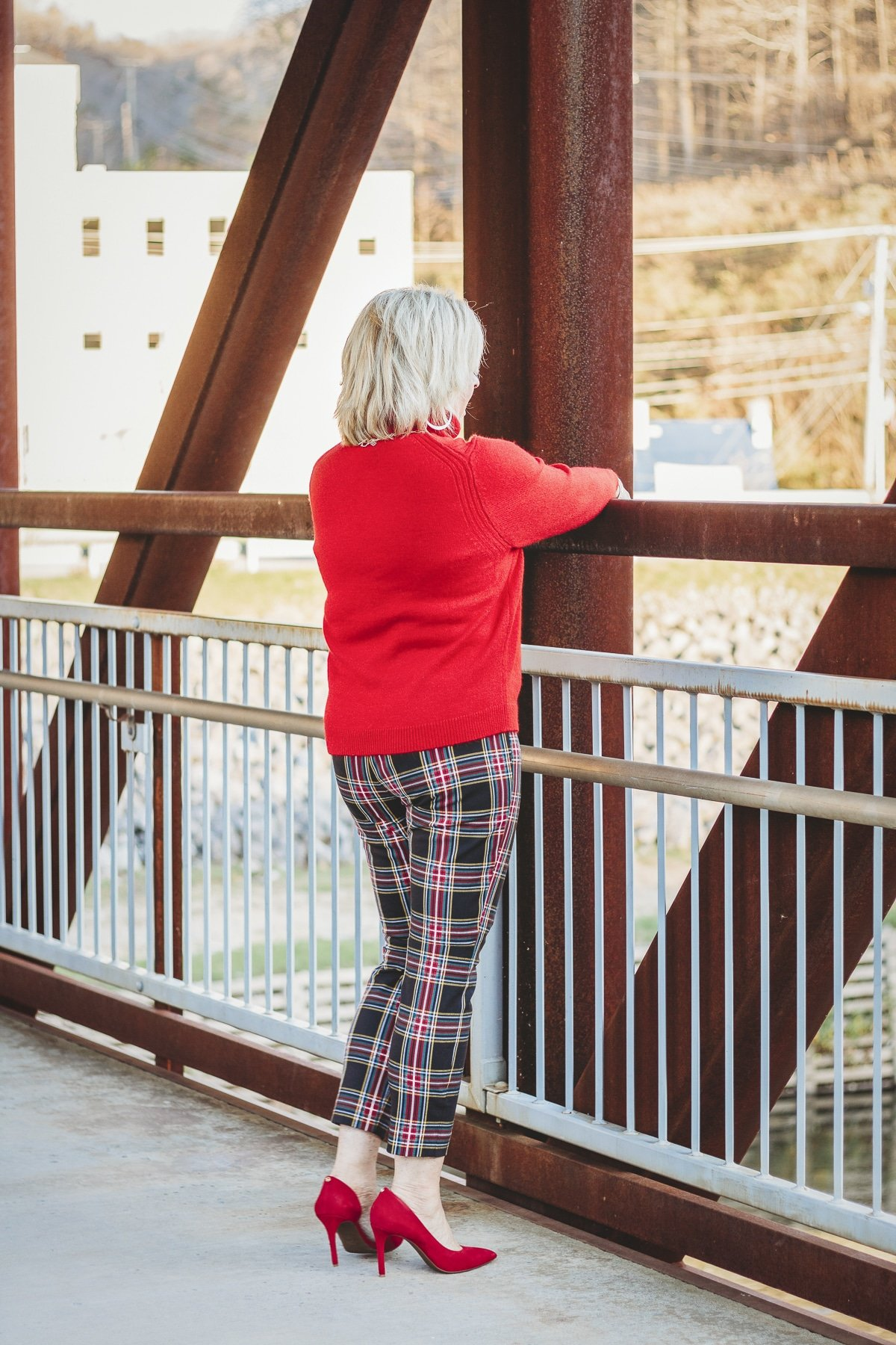 Fashion Blogger 50 Is Not Old is looking at the river in a red turtleneck sweater and plaid pants with red heels
