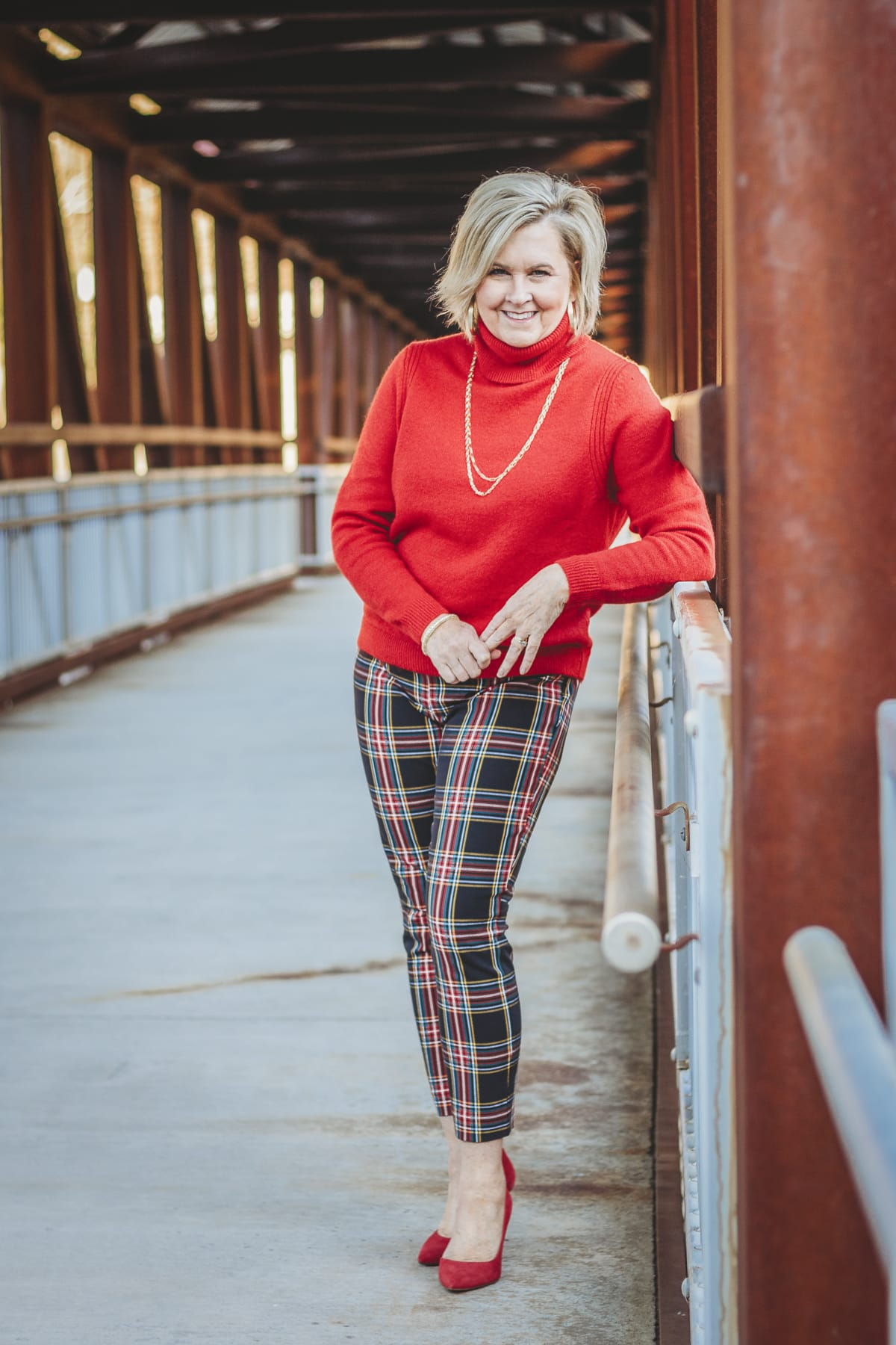 Fashion Blogger 50 Is Not Old is looking festive in this red turtleneck sweater and plaid pants