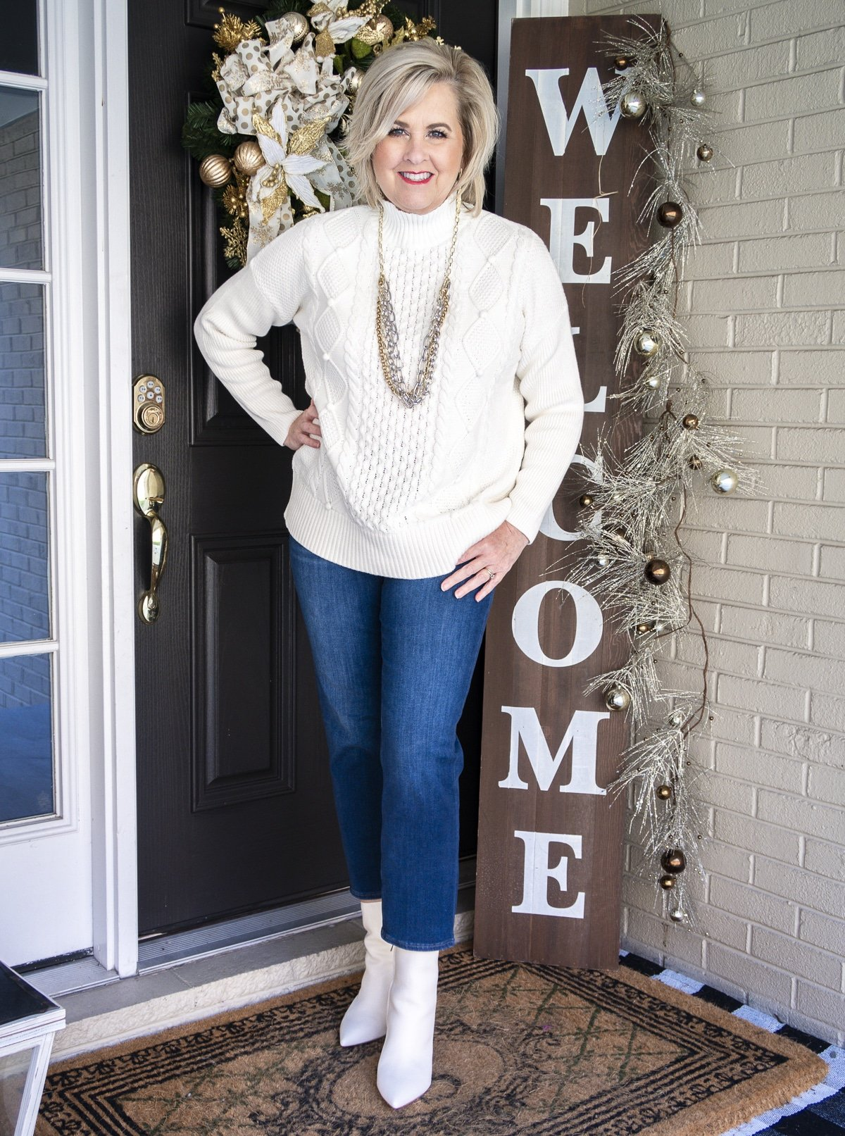 Fashion Blogger 50 Is Not Old is wearing a white cable-knit sweater, crop jeans, and white pointy toe ankle boots