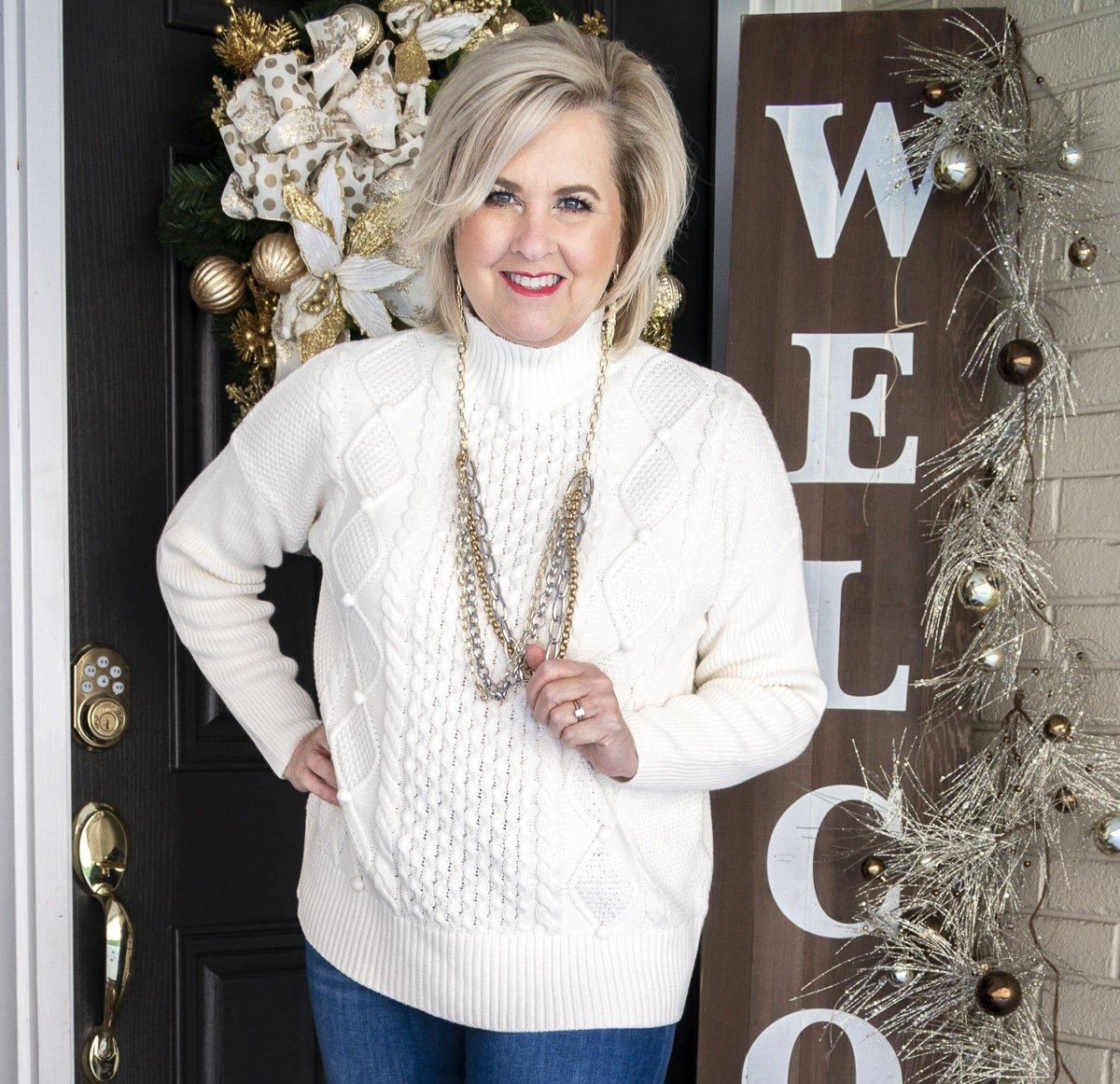 Fashion Blogger 50 Is Not Old is wearing a white cable-knit sweater and jewelry from Kendra Scott