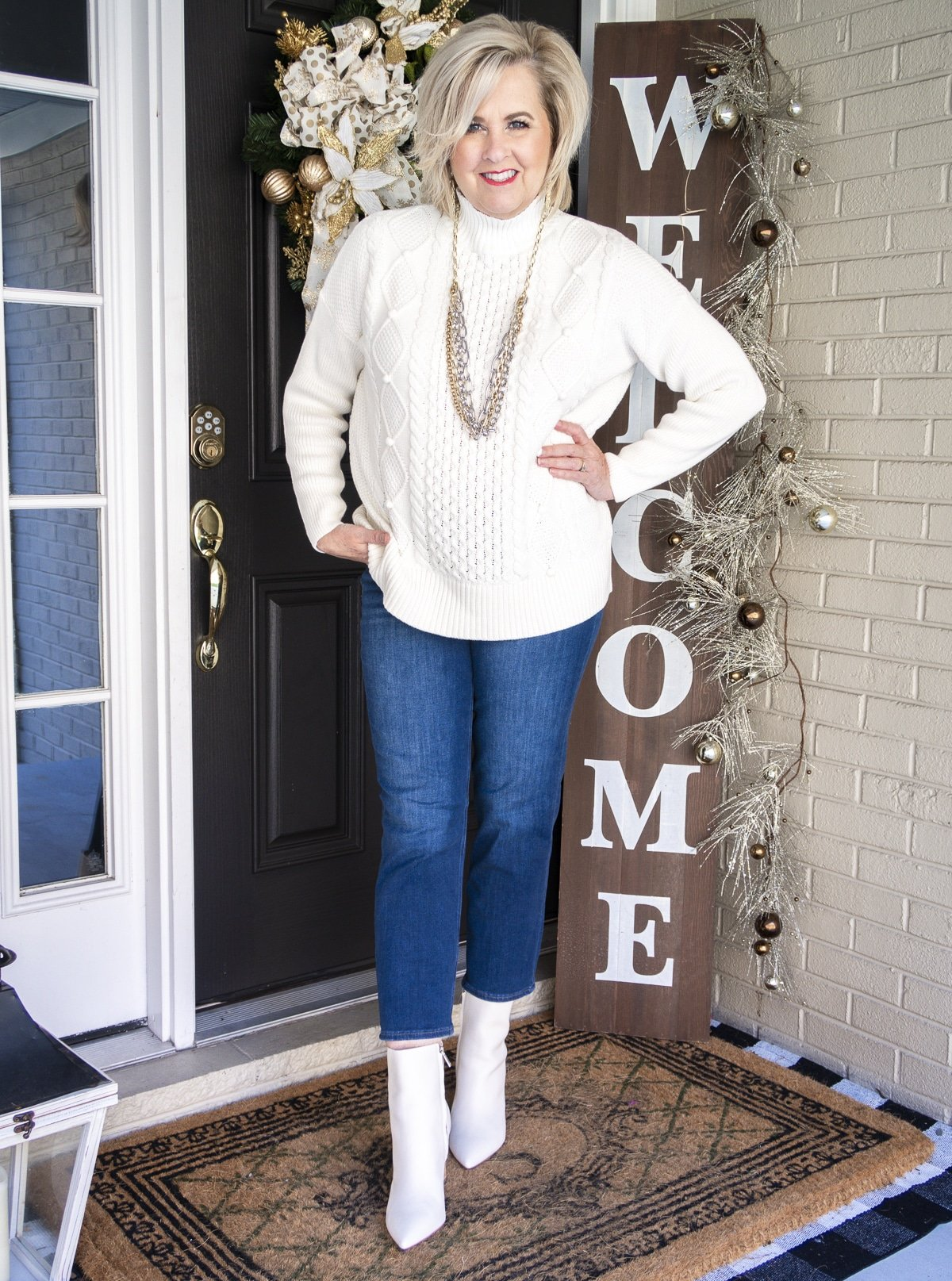 Fashion Blogger 50 Is Not Old is wearing a white cable-knit sweater, crop jeans, and white pointy toe ankle boots by Marc Fisher