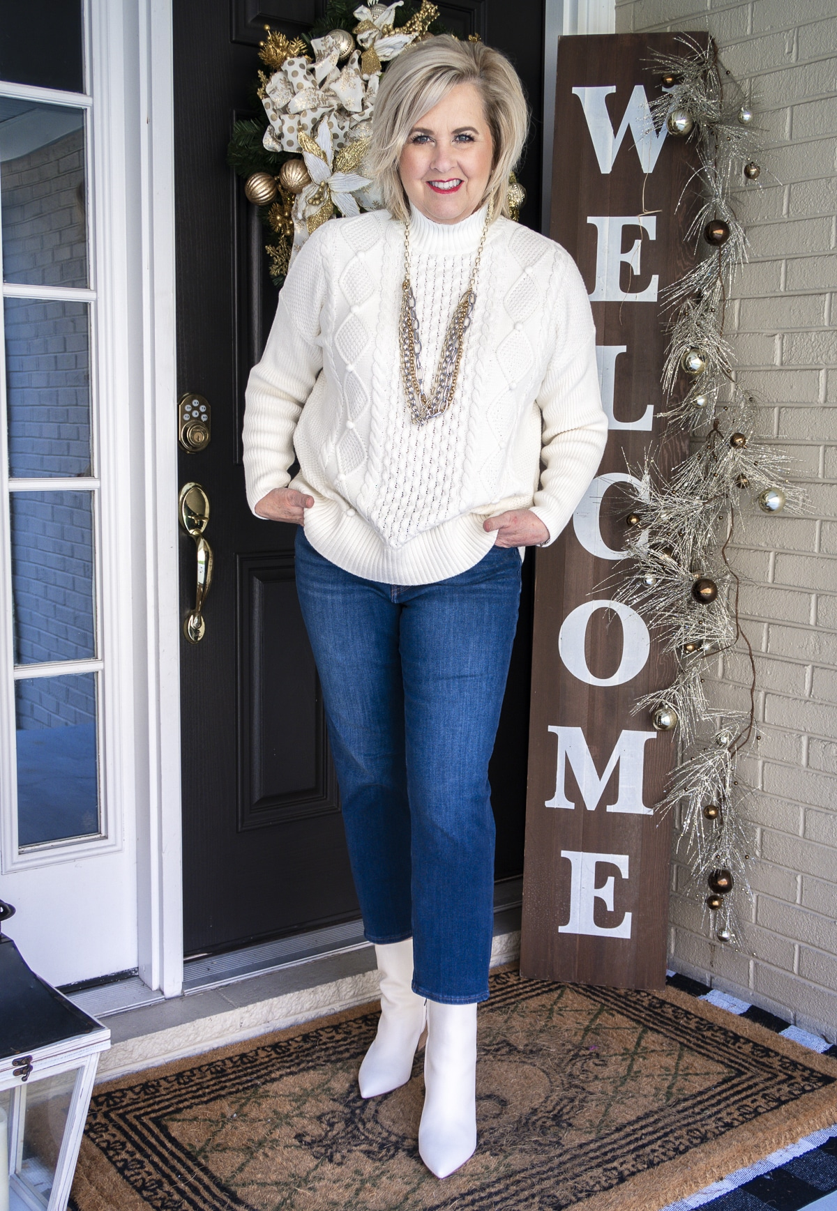 Fashion Blogger 50 Is Not Old is standing with her hands in her pockets and wearing a white cable-knit sweater, crop jeans, and white pointy toe ankle boots