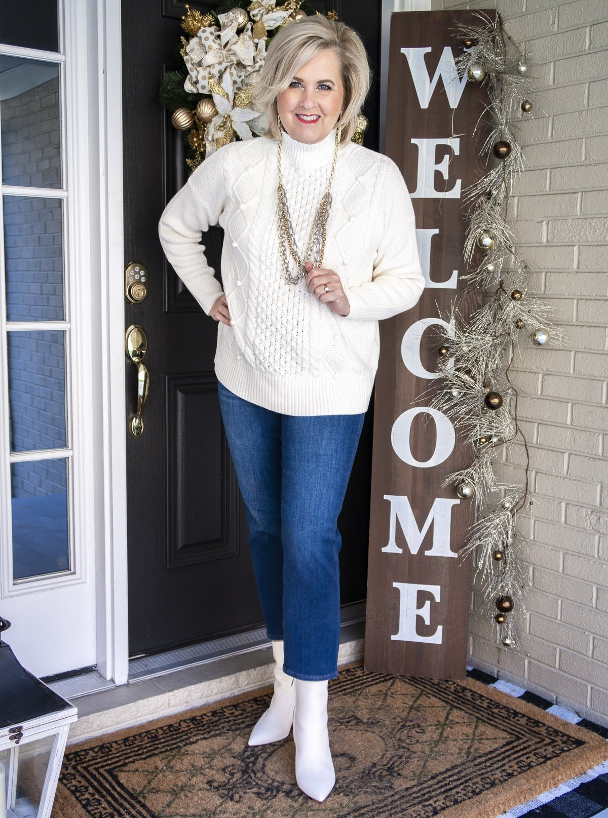 Fashion Blogger 50 Is Not Old is wearing a white cable-knit sweater, jewelry from Kendra Scott, crop jeans, and white pointy toe ankle boots