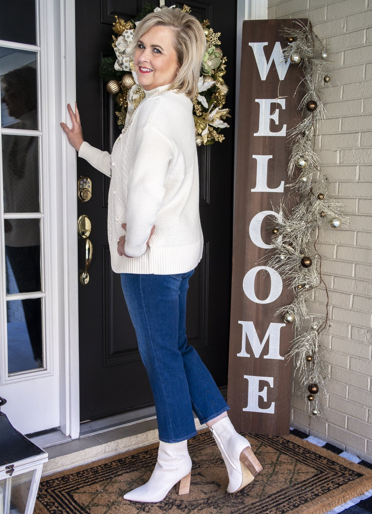 Fashion Blogger 50 Is Not Old is showing the back of a white cable-knit sweater, crop jeans, and white pointy toe ankle boots