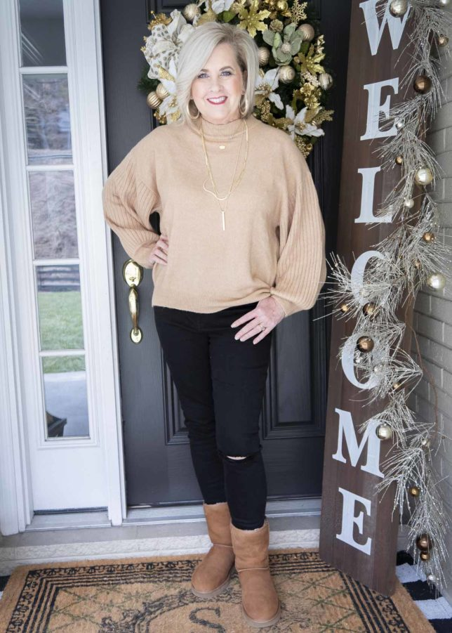 Fashion Blogger 50 Is Not Old wearing a brown sweater, black distressed jeans, and UGG Classic II boots
