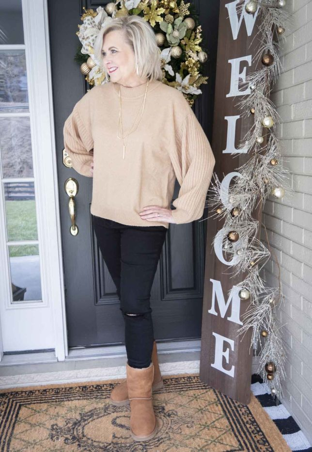 Fashion Blogger 50 Is Not Old is looking away in a brown sweater and black distressed jeans with UGG boots