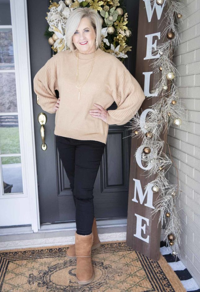 Fashion Blogger 50 Is Not Old wearing a brown sweater and black distressed jeans with UGG boots