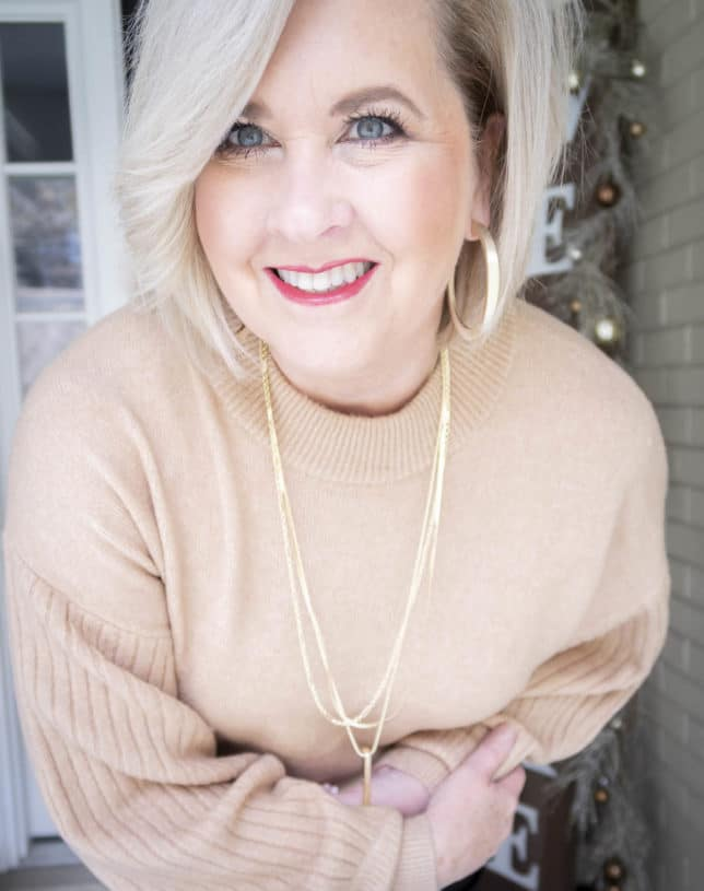 Fashion Blogger 50 Is Not Old wearing a brown sweater and gold jewelry from Kendra Scott
