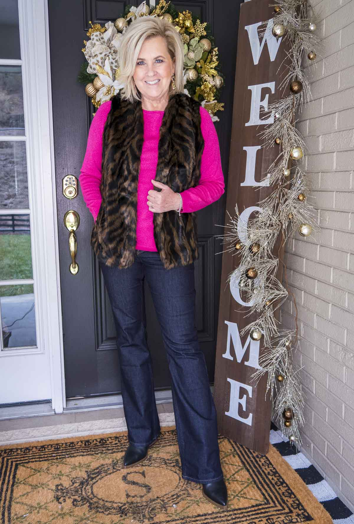 Over 40 Fashion Blogger 50 Is Not Old is wearing a bright pink sweater with a tiger print faux fur vest, flare jeans, and black pointy toe boots