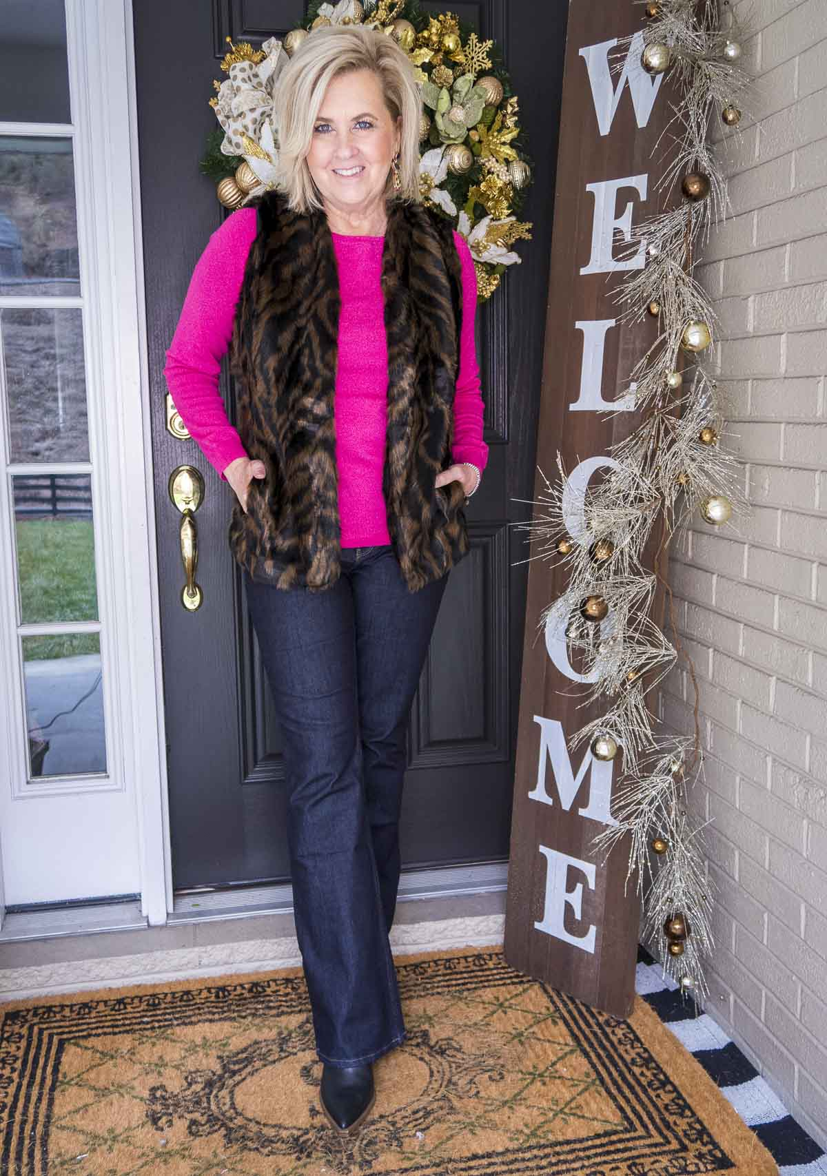 Over 40 Fashion Blogger 50 Is Not Old is wearing a bright pink sweater with a tiger print faux fur vest, flare jeans, and black pointy boots