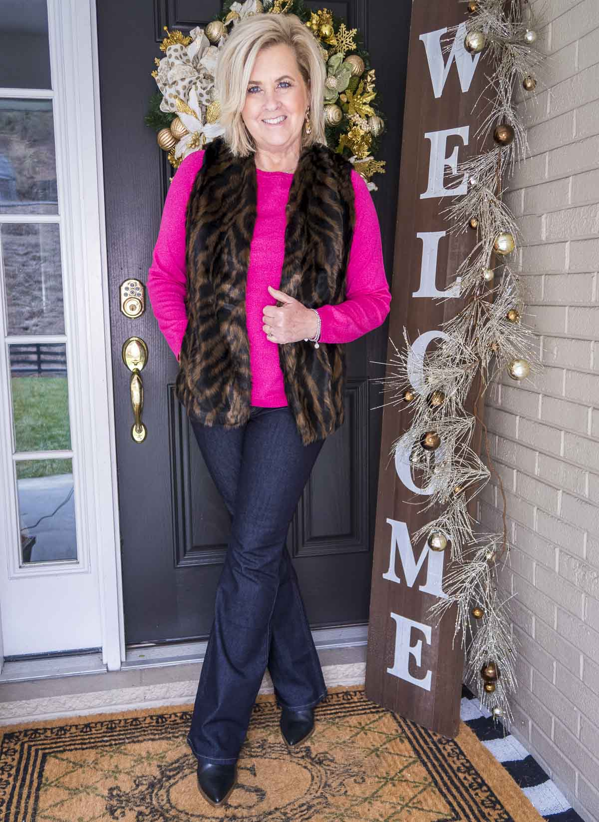 Over 40 Fashion Blogger 50 Is Not Old is wearing a pink sweater with a tiger print faux fur vest, flare jeans, and black pointy toe boots