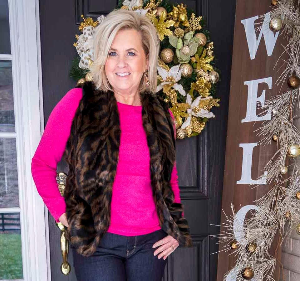 Over 40 Fashion Blogger 50 Is Not Old is wearing a bright color sweater with a tiger print faux fur vest