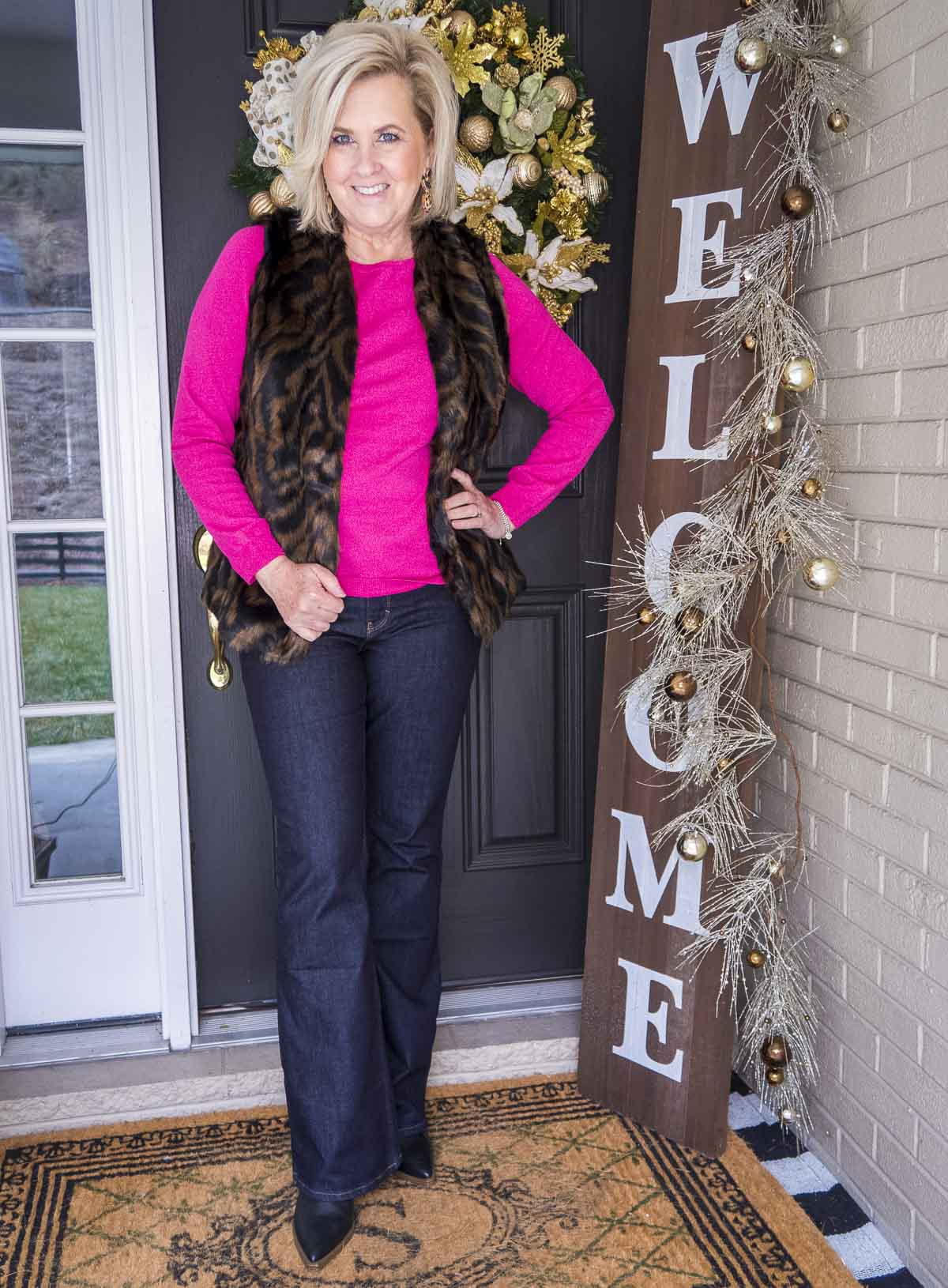 Over 40 Fashion Blogger 50 Is Not Old is wearing a pink sweater with a tiger print faux fur vest, flare jeans, and black ankle boots