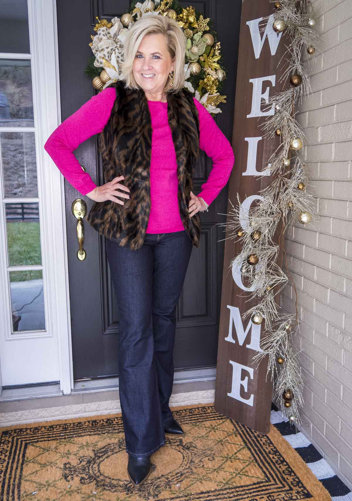 Over 40 Fashion Blogger 50 Is Not Old has her hands on her hips wearing a bright pink sweater with a tiger print faux fur vest, flare jeans, and black pointy toe boots
