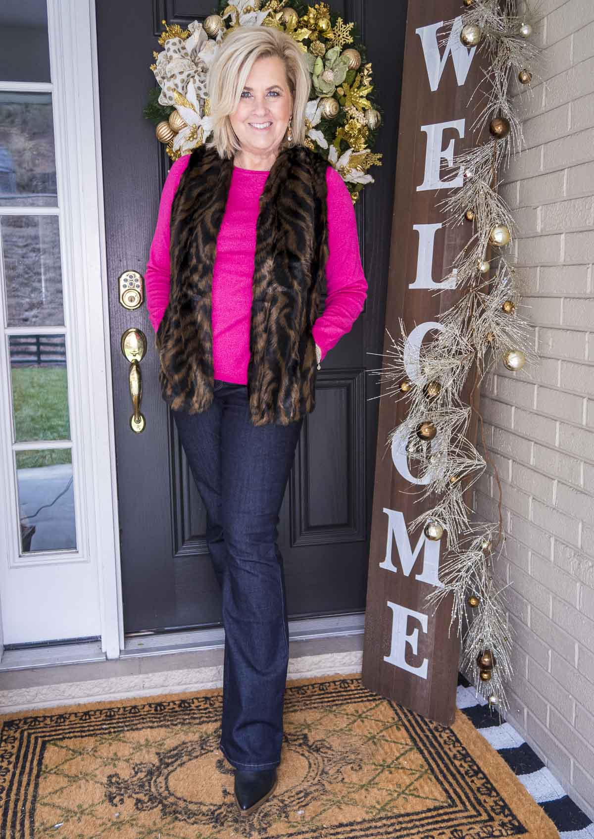 Over 40 Fashion Blogger 50 Is Not Old is wearing a bright pink sweater with a tiger print faux fur vest, flare jeans, and black boots