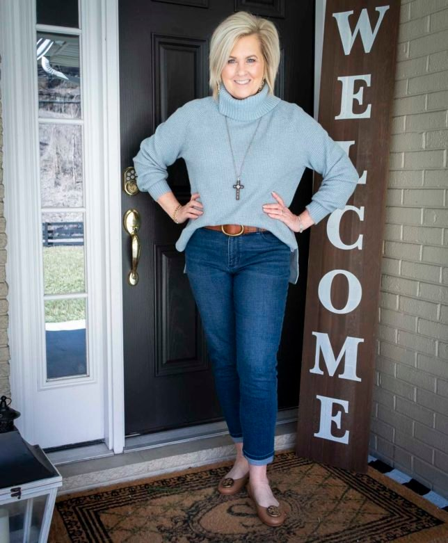Fashion Blogger 50 Is Not Old is wearing a blue waffle knit cowl-neck sweater, relaxed jeans, ballet flats, and a brown leather belt