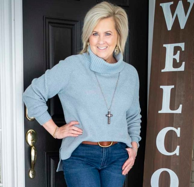 Fashion Blogger 50 Is Not Old is wearing a blue waffle knit cowl-neck sweater and a wooden cross