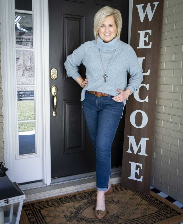 Fashion Blogger 50 Is Not Old is wearing a blue waffle knit cowl-neck sweater, relaxed jeans, ballet flats, and a wooden cross