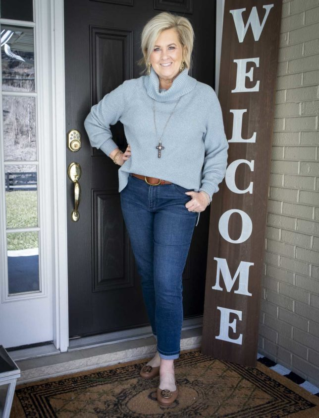 Fashion Blogger 50 Is Not Old is wearing a blue waffle knit cowl-neck tunic sweater, relaxed jeans, ballet flats, and a brown leather belt