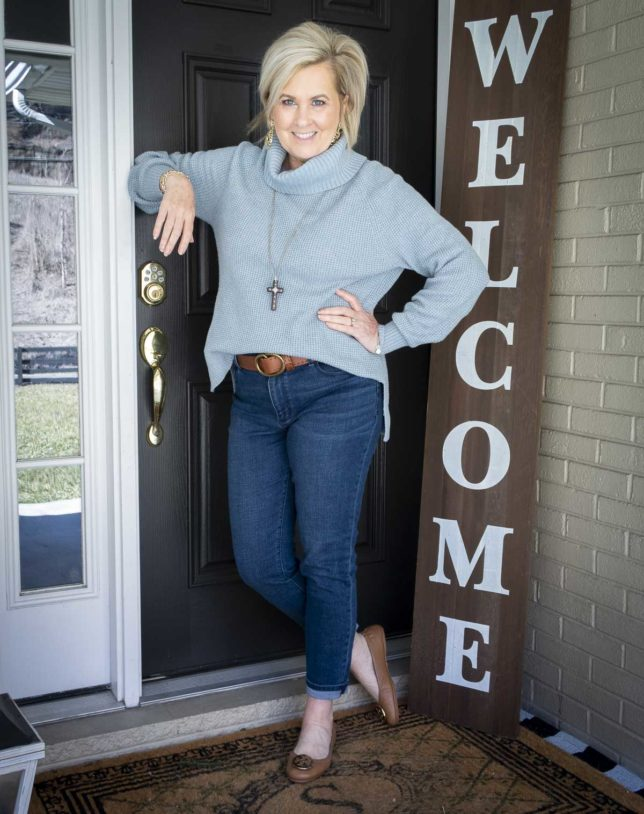 Fashion Blogger 50 Is Not Old is leaning against the door while wearing a blue waffle knit cowl-neck sweater, relaxed jeans, ballet flats, and a brown leather belt