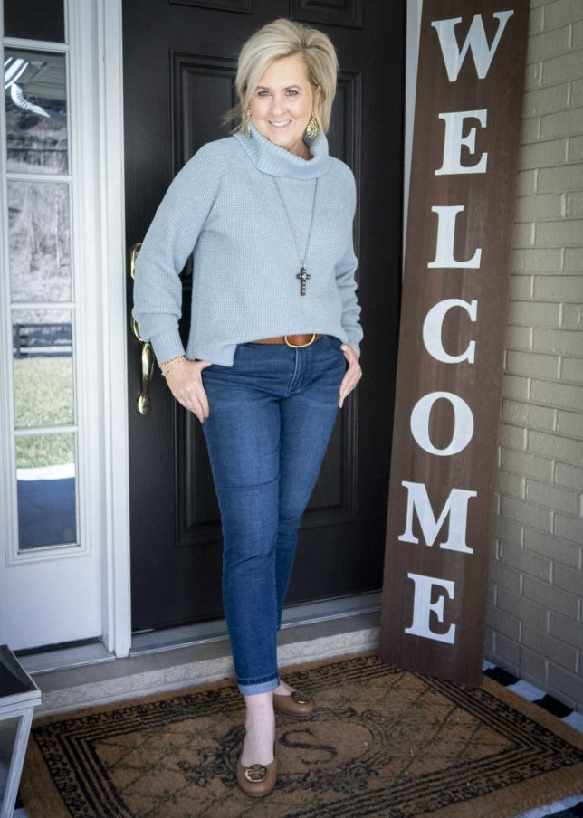 Fashion Blogger 50 Is Not Old is wearing a blue waffle knit cowl-neck sweater, girlfriend jeans, ballet flats, and a brown leather belt