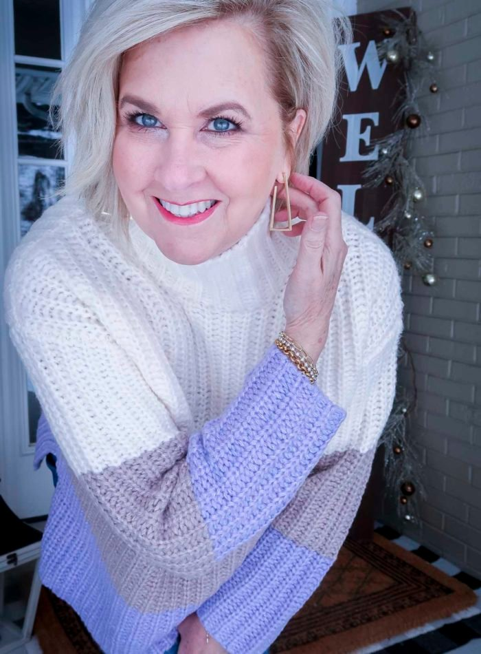 Fashion Blogger 50 Is Not Old is wearing a chunky knit colorblock sweater with gold earrings