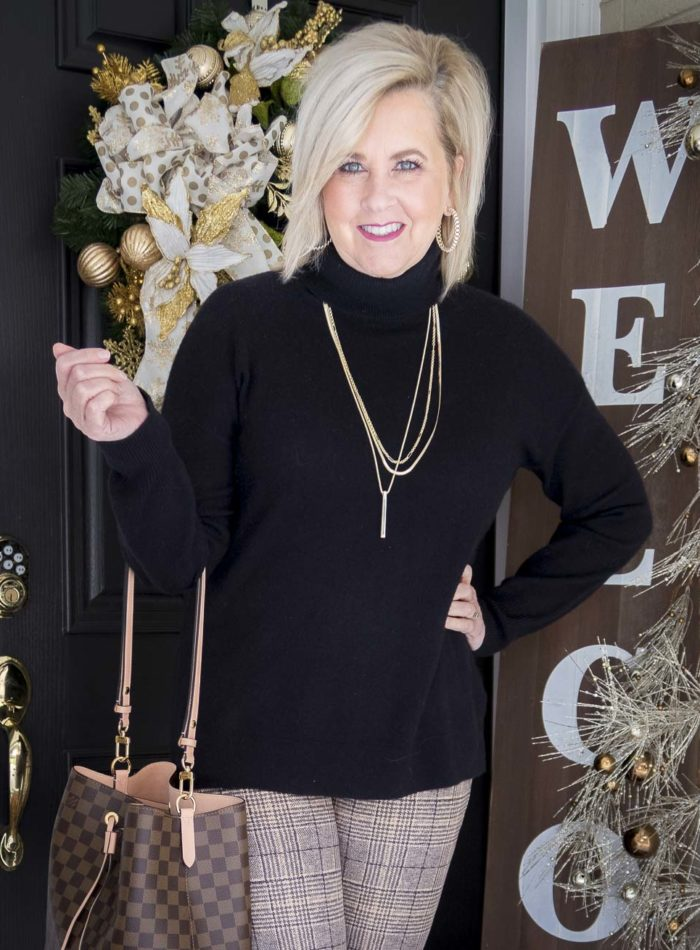 Fashion Blogger 50 Is Not Old is wearing a black cashmere turtleneck with a Louis Vuitton handbag
