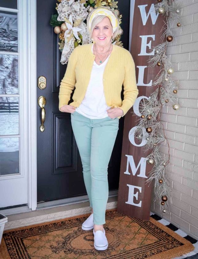 Fashion Blogger 50 Is Not Old is wearing a yellow up cardigan, a white v-neck tee, a yellow and white scarf in her hair, and mint green jeans with white pull-on sneakers from Target