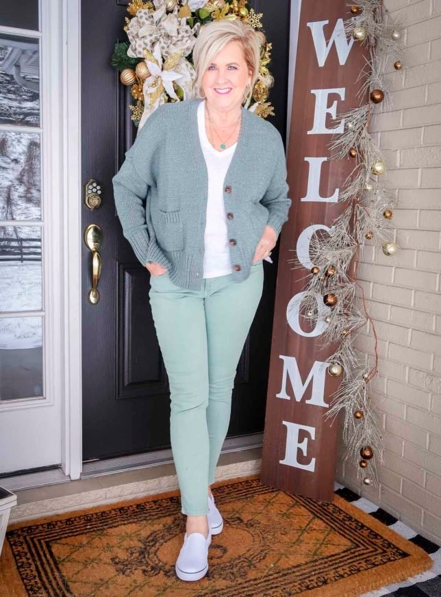 Fashion Blogger 50 Is Not Old is wearing a green button up cardigan, a white v-neck tee, and mint green jeans with white sneakers