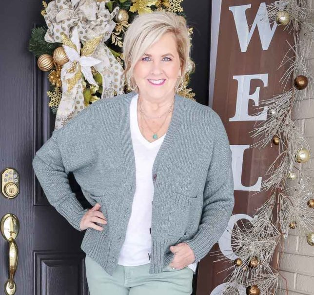 Fashion Blogger 50 Is Not Old is wearing a green button up cardigan and a white v-neck tee