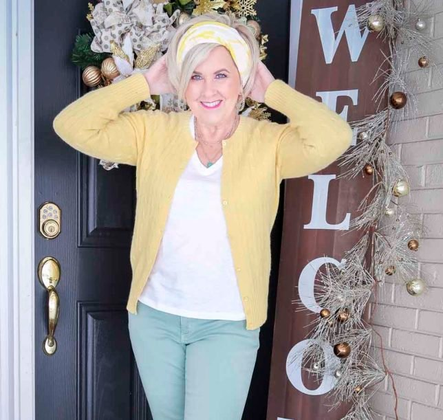 Fashion Blogger 50 Is Not Old is wearing a yellow up cardigan, a white v-neck tee, a yellow and white scarf in her hair, and mint green jeans with white pull-on sneakers
