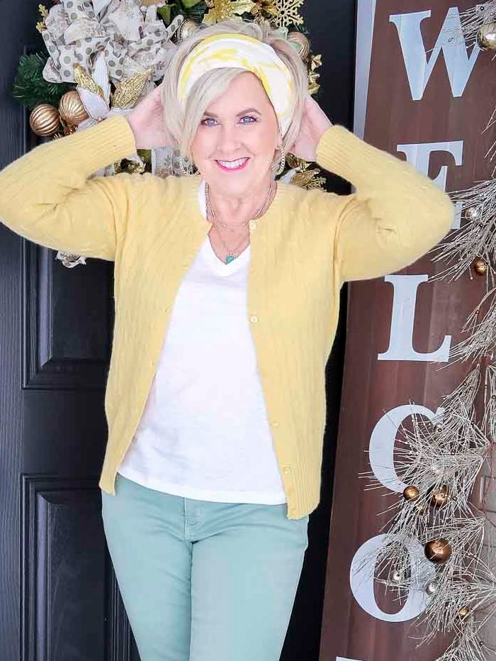 Fashion Blogger 50 Is Not Old is wearing a yellow up cardigan, a white v-neck tee, a yellow and white scarf in her hair, and mint green jeans
