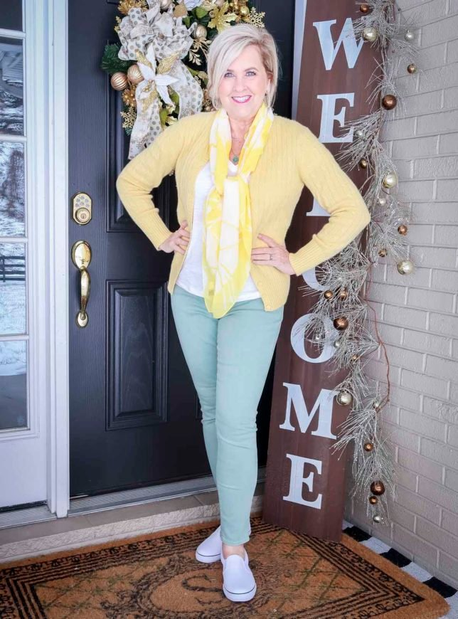 Fashion Blogger 50 Is Not Old is wearing a yellow up cardigan, a white v-neck tee, a yellow and white scarf around her neck, and mint green jeans with white pull-on sneakers