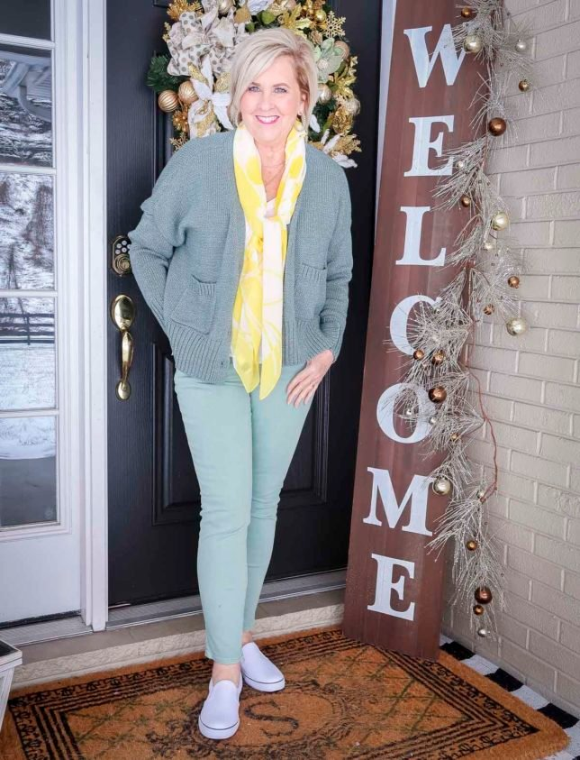 Fashion Blogger 50 Is Not Old is wearing a green button up cardigan, a white v-neck tee, a yellow and white scarf, and mint green jeans with white pull-on sneakers