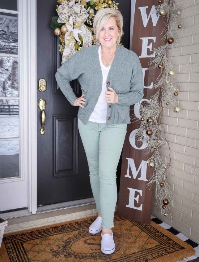 Fashion Blogger 50 Is Not Old is wearing a green button up cardigan, a white v-neck tee, and mint green jeans with white pull-on sneakers