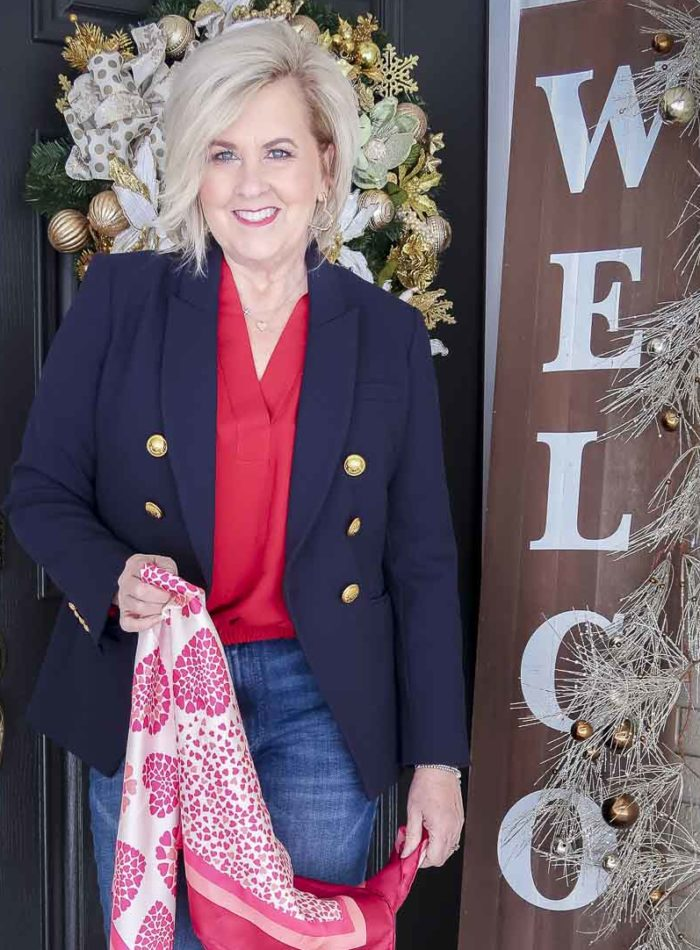 Fashion Blogger 50 Is Not Old is wearing a red blouse with a navy blazer, and a heart scarf