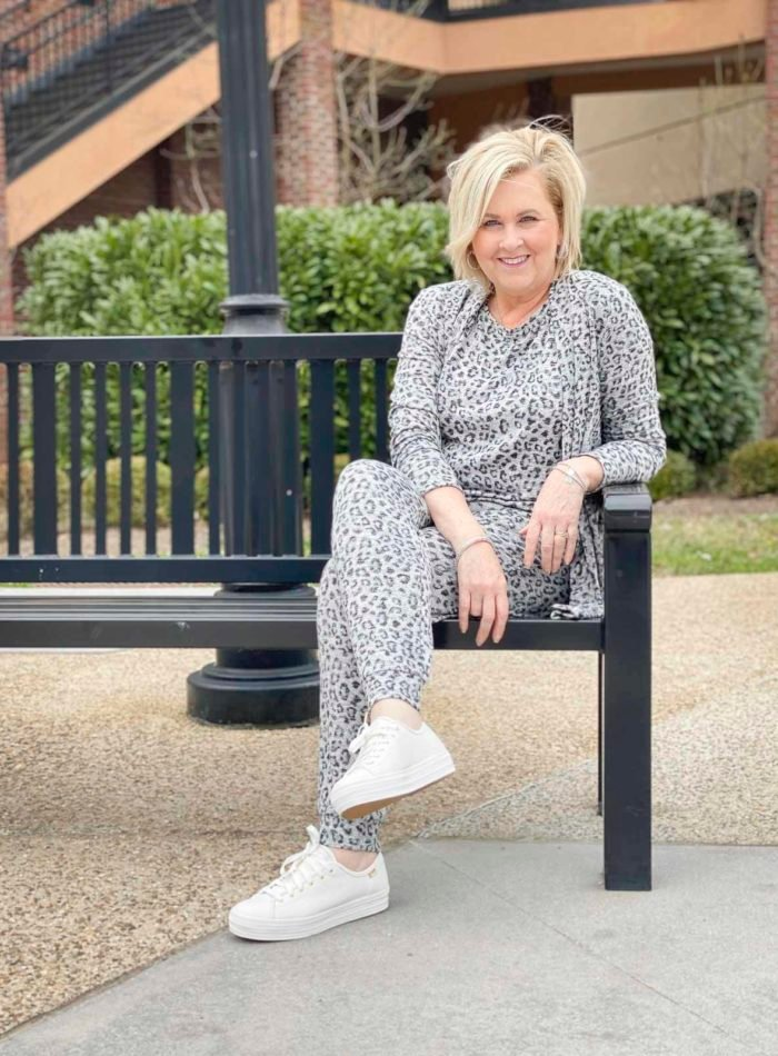 Fashion Blogger 50 Is Not Old is sitting on a bench wearing animal print luxe loungewear from Chico's and Ked's platform sneakers