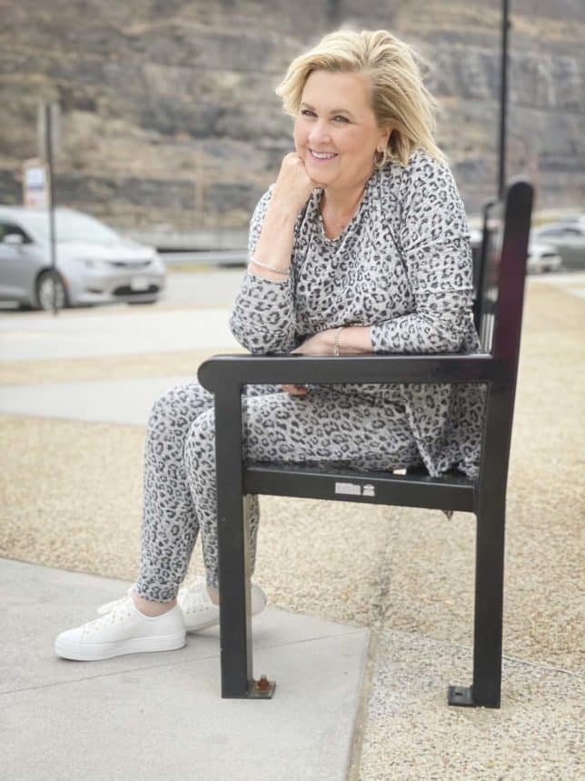Fashion Blogger 50 Is Not Old is wearing a gray animal print luxe loungewear set from Chico's and Ked's platform sneakers