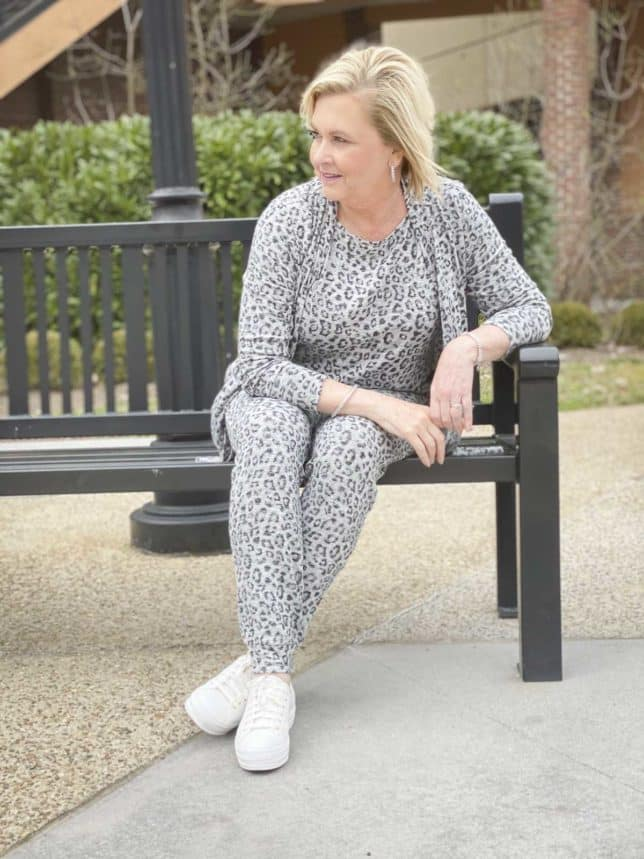 Fashion Blogger 50 Is Not Old is sitting on a black bench and wearing animal print loungewear from Chico's and Ked's platform sneakers