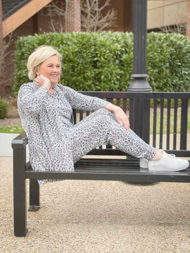 Fashion Blogger 50 Is Not Old is sitting with her feet on a bench and wearing animal print luxe loungewear from Chico's and Ked's platform sneakers