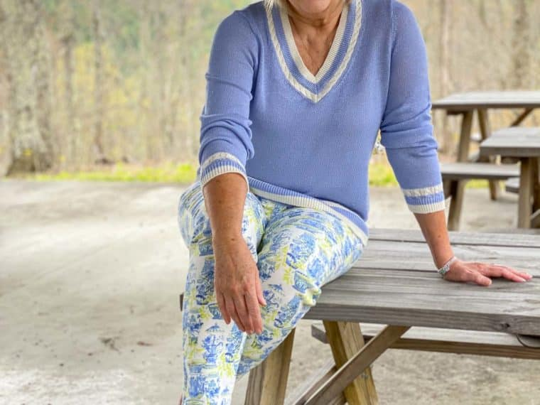 Fashion Blogger 50 Is Not Old let her husband pick out her outfit, and she is sitting on a table wearing a sky blue v-neck sweater with ankle prints with blue vases on them
