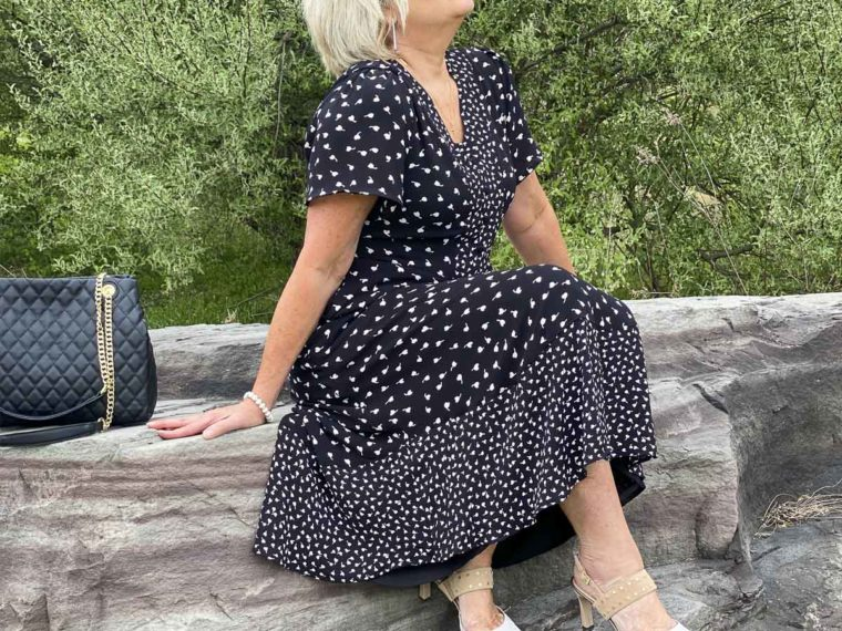 Fashion Blogger 50 Is Not Old is sitting on a rock wearing a black and white print dress from Talbots with beige and white heels