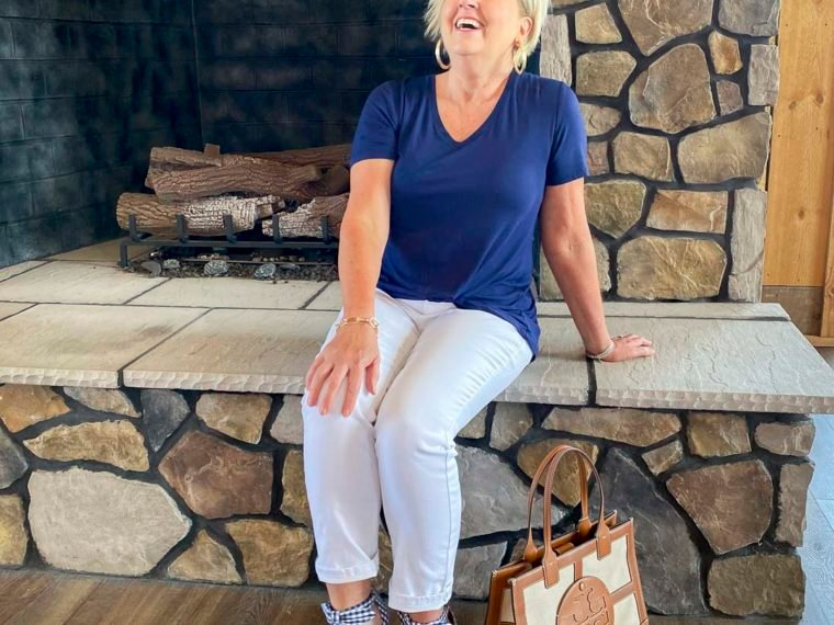 Fashion Blogger 50 Is Not Old is sitting on a fireplace laughing and wearing a navy top, white jeans, and gingham bow heels