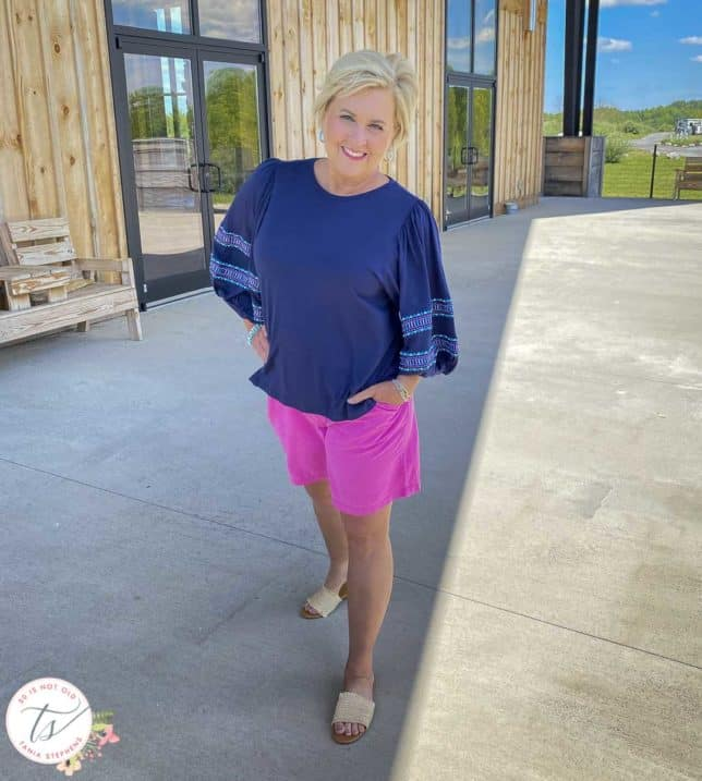 Fashion Blogger 50 Is Not Old is wearing a pair of pink shorts, a navy top with embroidered balloon sleeves, and raffia slide sandals