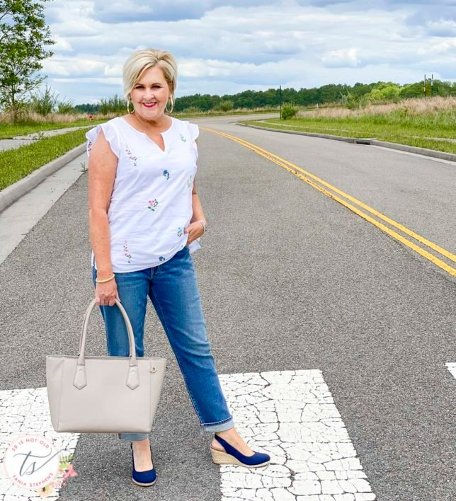 Fashion Blogger 50 Is Not Old is wearing an embroidered white top and boyfriend jeans