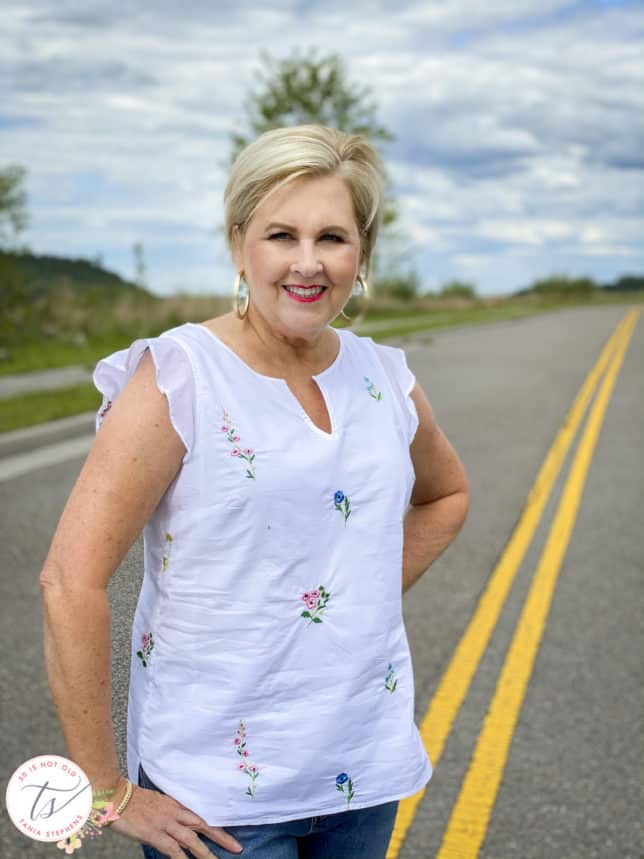 Fashion Blogger 50 Is Not Old is wearing an embroidered white top