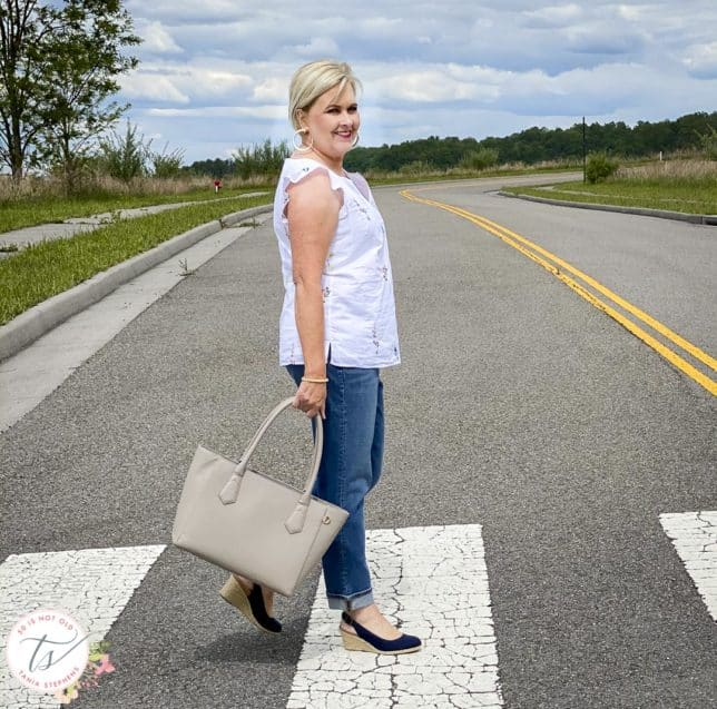 Fashion Blogger 50 Is Not Old is wearing an embroidered white top, boyfriend jeans, and carrying a Dagne Dover tote