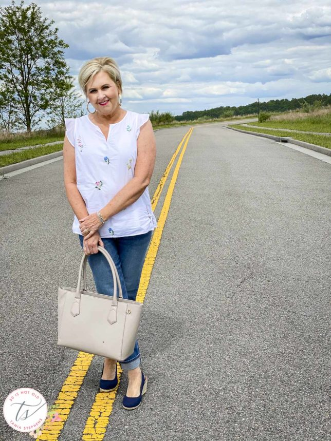 Fashion Blogger 50 Is Not Old is walking the line with a feminine white top and boyfriend jeans