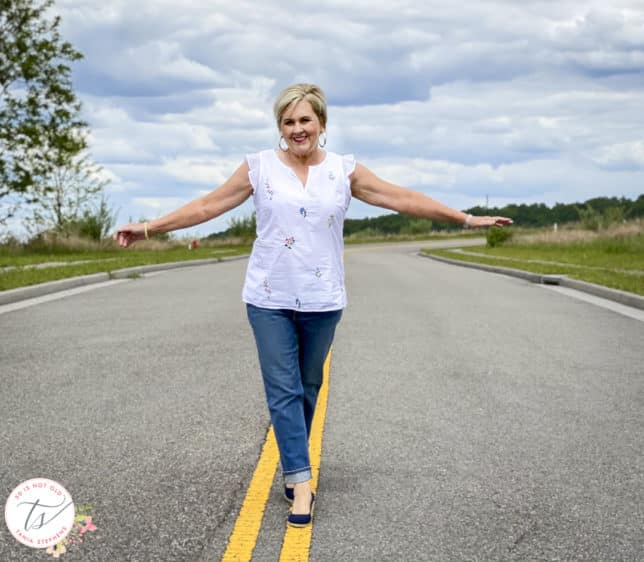 Fashion Blogger 50 Is Not Old is walking the line in a feminine white top and boyfriend jeans